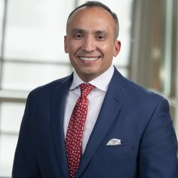 Carlos Gutierrez Headshot in suit and red tie