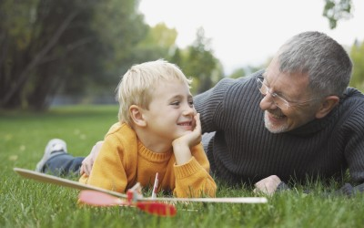 grandfather and grandchild laying on grass with a toy airplane