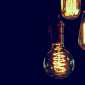 three edison lightbulbs on a dark blue background