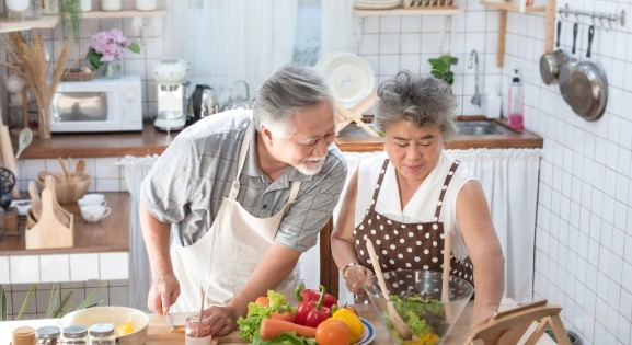 elderly couple of east Asian descent cooking together